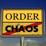 A sign with chaos and order on it - it's decluttering home time.