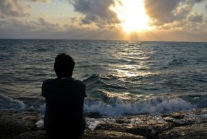 A man siting on the beach watching sunset