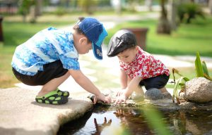 Toddlers playing by the pond