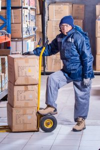 A man posing with boxes before purchasing moving insurance