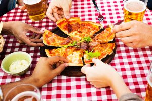 Five people taking a slice of pizza each.