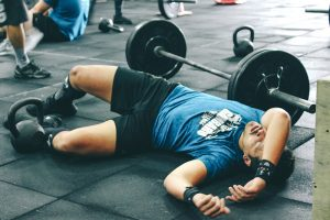 A man laying on the floor of the gym