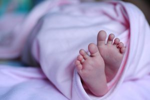 A little kid wrapped in pink blanket with feet poking out