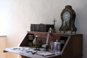 Antique table, clock, coffin, feather and paper.