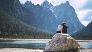 2 people on the rock by the water, looking at woods and mountains.